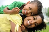image of family fun  - African American mother and son having fun playing in park - JPG