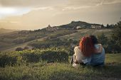 young lovers embraced sitting in the countryside admiring panorama