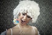 picture of nasty  - Nasty girl in white angel costume bites lollipop for a nasty surprise in Valentine - JPG