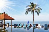 The luxurious marble pool on the island of Koh Samui. Palm tree and beach chairs are reflected in th