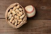 A bag of peanuts and a baseball on an old wooden bench at the ballpark. Horizontal format with copy