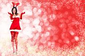 stock photo of boxing day  - Santa helper woman over red christmas background - JPG