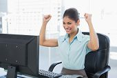 Elegant and happy businesswoman clenching fists while looking at computer in a bright office