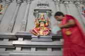 stock photo of lakshmi  - An old Indian woman worshipping the colorful stone wall statue of the Hindu deity Lakshmi Goddess of wealth prosperity light wisdom fortune fertility generosity and courage - JPG