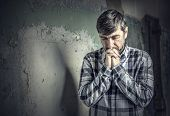 foto of praying  - man praying on the background of old wall - JPG