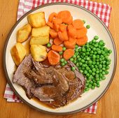 Roast lamb dinner with vegetables and gravy.