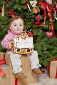 Little girl sits on big cardboard gift box under Christmas tree, holding gingerbread house in her ha