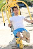 Man exercising with outdoors weight machines