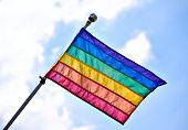 foto of gay pride  - Rainbow Gay Pride Flag waiving on sunny cloudy blue sky background - JPG
