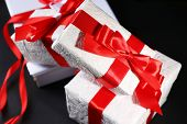 Beautiful gifts with red ribbons, on dark background