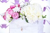 Beautiful wedding flowers in crate on bright background