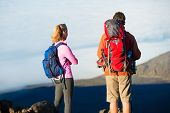 Two hikers relaxing enjoying the amazing view from the mountain top. Looking out over the volcano cr