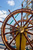 pic of wind wheel  - Steering wheel of the ship on blue sky with white clouds - JPG