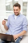 technology, home and lifestyle concept - smiling man working with laptop and credit card at home