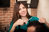 stock photo of barber  - Beautiful female barber giving a haircut to a client at a barber shop - JPG