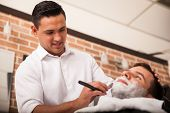 stock photo of barber  - Handsome Latin barber shaving another man - JPG