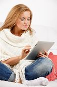 woman using tablet and sitting on sofa at home