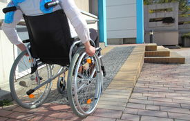 stock photo of handicapped  - Woman in a wheelchair using a ramp - JPG