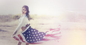 picture of denim wear  - Beautiful young woman wearing denim shirt holding American flag in the open desert - JPG
