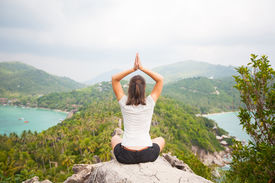 stock photo of samadhi  - Yoga meditation in yoga pose by woman on the peak of mountain - JPG