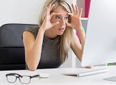 stock photo of  eyes  - Tired woman barely keeps her eyes open in front of computer - JPG