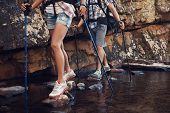 stock photo of dam  - Cropped image of a hiking woman and man crossing a dam by balancing on the rocks in the dam - JPG