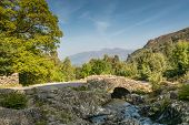 foto of ashes  - Ashness Bridge with Derwent Water Keswick and Mount Skiddaw beyond is an old single track packhorse bridge - JPG