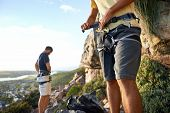 stock photo of harness  - Cropped image of two men putting on their harness and rock climbing equipment - JPG