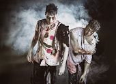 image of zombie  - Two male zombies standing on black smoky background looking at camera - JPG
