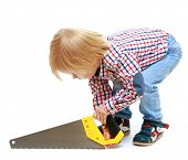 stock photo of sawing  - Little boy sawing saw - JPG