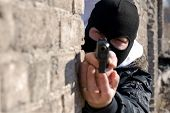 stock photo of glock  - Criminal in black mask targeting at you with semi - JPG