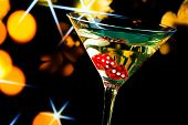 image of dice  - red dice in the cocktail glass on gold bokeh and stars background - JPG