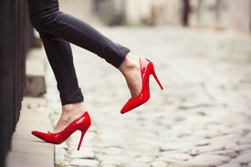 stock photo of stiletto  - Woman wearing black leather pants and red high heel shoes in old town - JPG