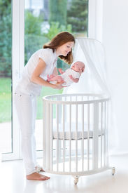 picture of canopy  - Young Mother Putting Her Newborn Baby To Sleep In A White Round Crib With Canopy Next To A Big Window - JPG