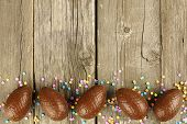 picture of easter candy  - Chocolate Easter egg bottom border over a wood background - JPG