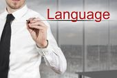 stock photo of pronunciation  - businessman in office writing language in the air - JPG