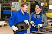 pic of welding  - Instructor teaching trainee or worker how to weld metal