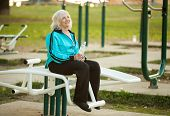 stock photo of 70-year-old  - 70 years old Healthy Senior Woman Resting after Exercises Outdoors in the Bright Autumn Evening - JPG
