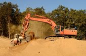stock photo of track-hoe  - Large track hoe excavator loading a articulated dump truck with dirt from a new commercial development construction project - JPG