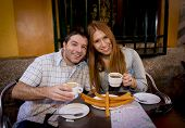 stock photo of churros  - young beautiful American tourist couple having spanish typical breakfast hot chocolate with churros smiling happy in tourism and holidays travel in Europe concept - JPG