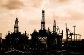 pic of oil drilling rig  - Oil Drilling Rig Silhouette over a Cloudy Sky - JPG