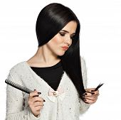 picture of split ends  - Sad brunette young woman holding her hair and a comb - JPG