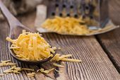 picture of grating  - Cheddar Cheese (grated) as close-up shot on an old vintage wooden table