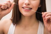 picture of human teeth  - Young woman in front of a mirror is brushing her teeth - JPG