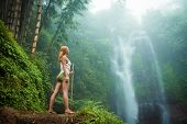 picture of adults only  - Female adventurer looking at waterfall in Bali jungle - JPG