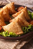 picture of samosa  - samosa on a plate with tomatoes and lettuce on a wooden table - JPG