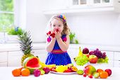 pic of healthy eating girl  - Cute curly little girl in a colorful summer dress eating fresh tropical fruit and berry for healthy breakfast snack in a white sunny family kitchen - JPG