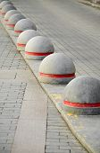 pic of paving stone  - Round stone road kerb with a red strip standing in a row and on a diagonal on a paving stone - JPG