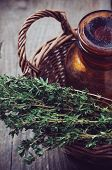 foto of wooden basket  - Brown glass pharmacy bottle and thyme herb in a wicker basket vintage style on old wooden board.