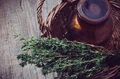 image of wooden basket  - Brown glass pharmacy bottle and thyme herb in a wicker basket vintage style on old wooden board.